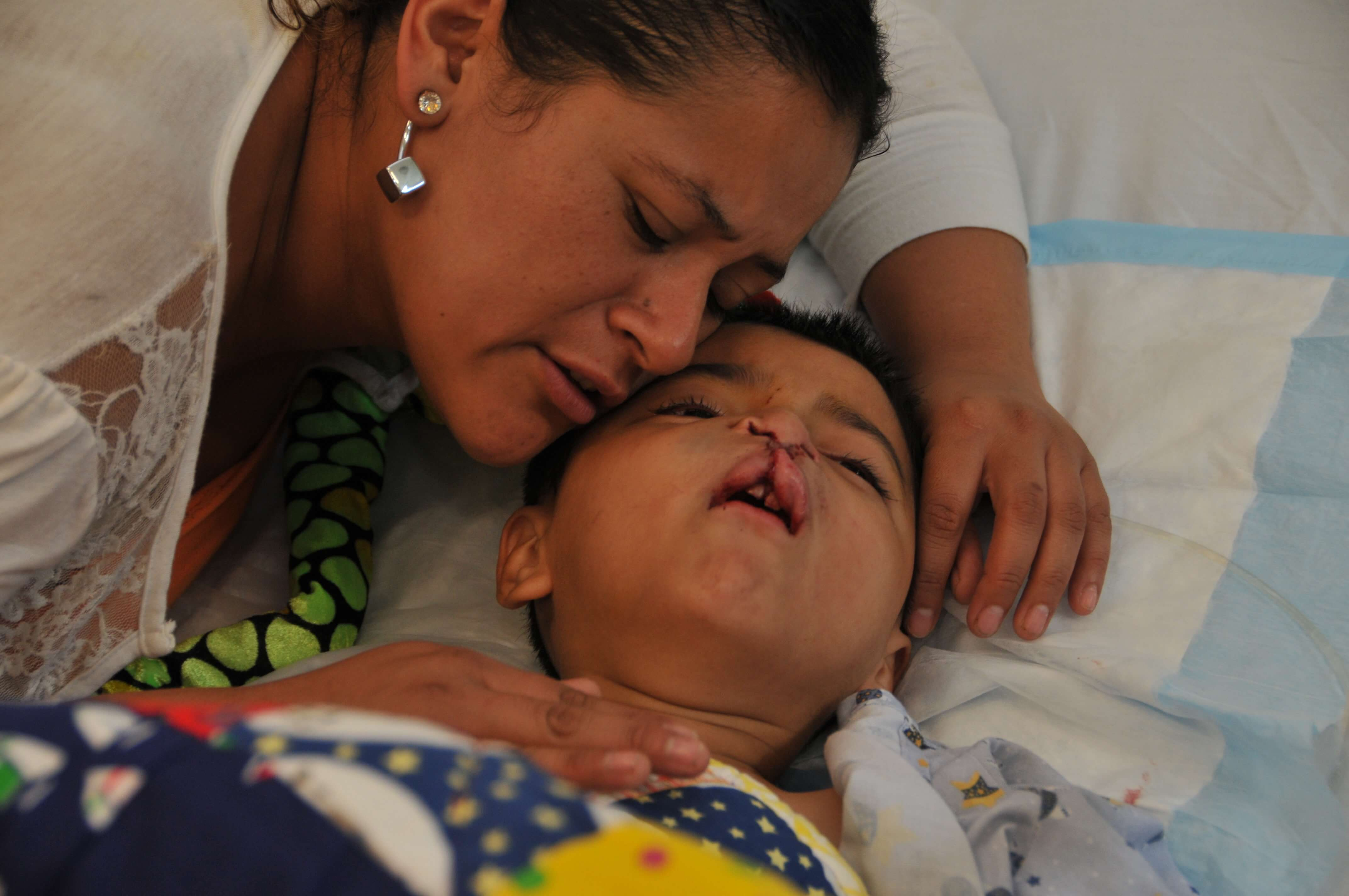 A mother comforts her son after surgery.