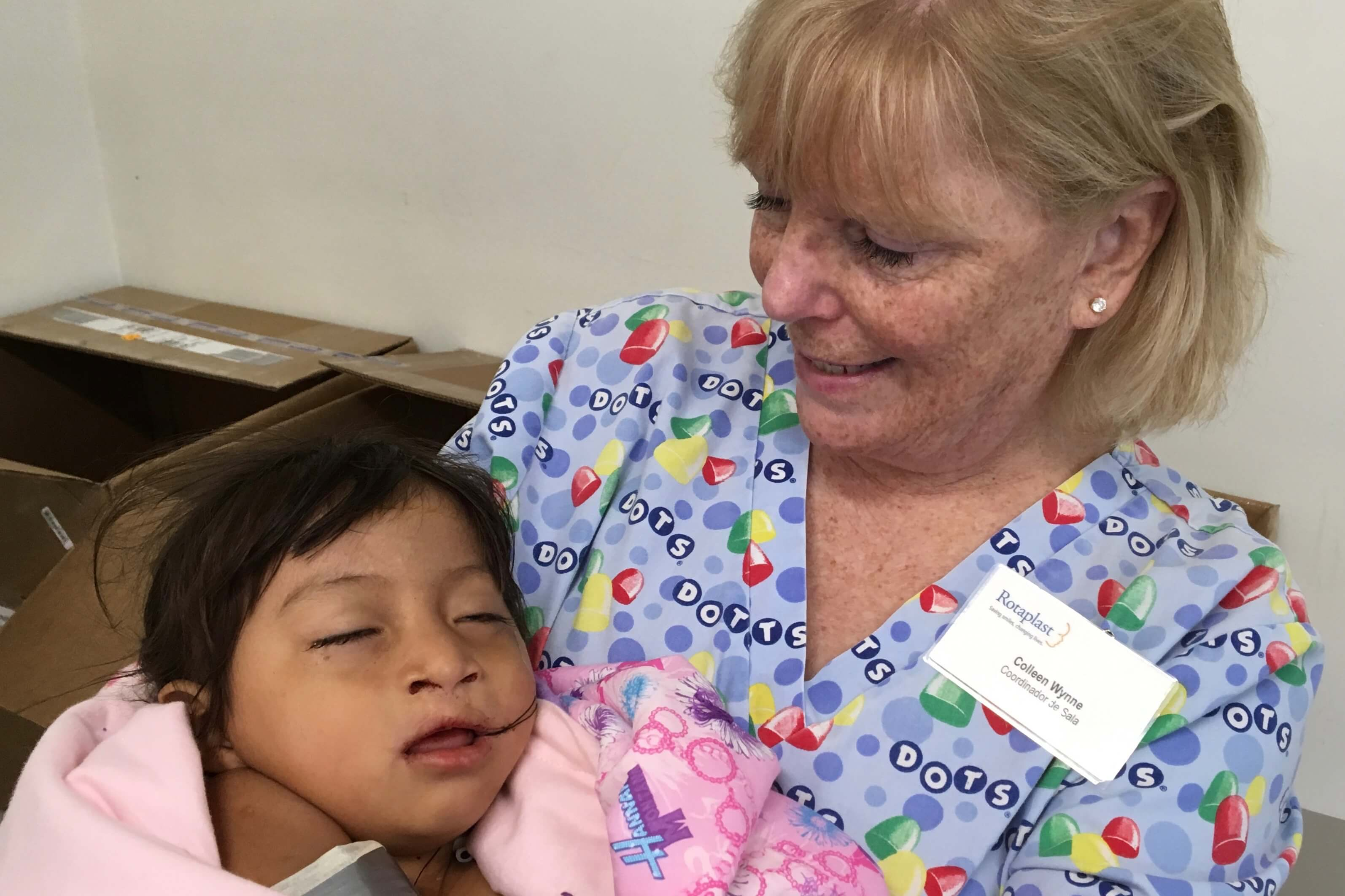 Colleen Wynne of Los Altos, CA holds a child after cleft palate repair.
