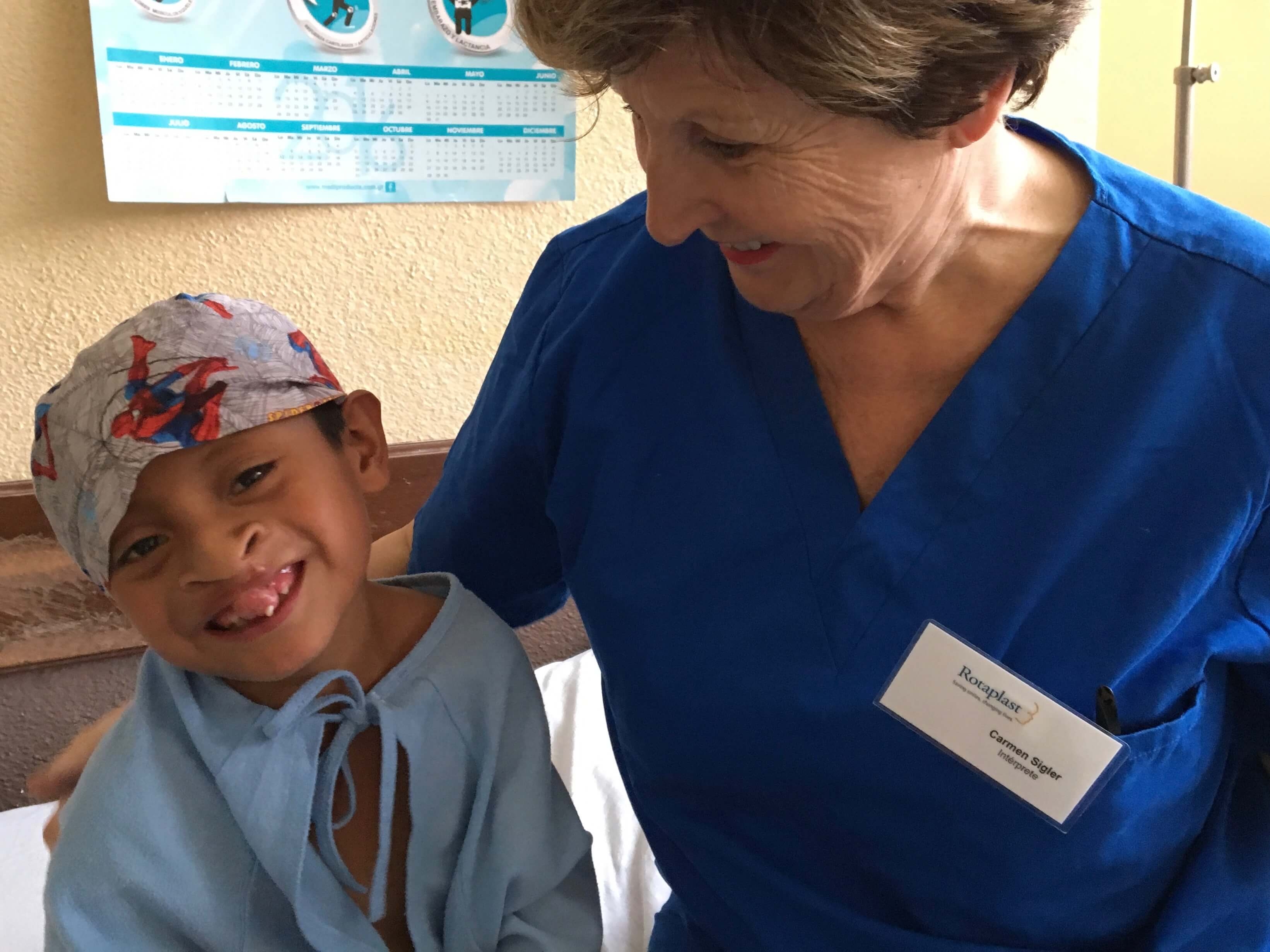 Translator and San Jose Rotarian Carmen Sigler plays with a patient before his surgery.