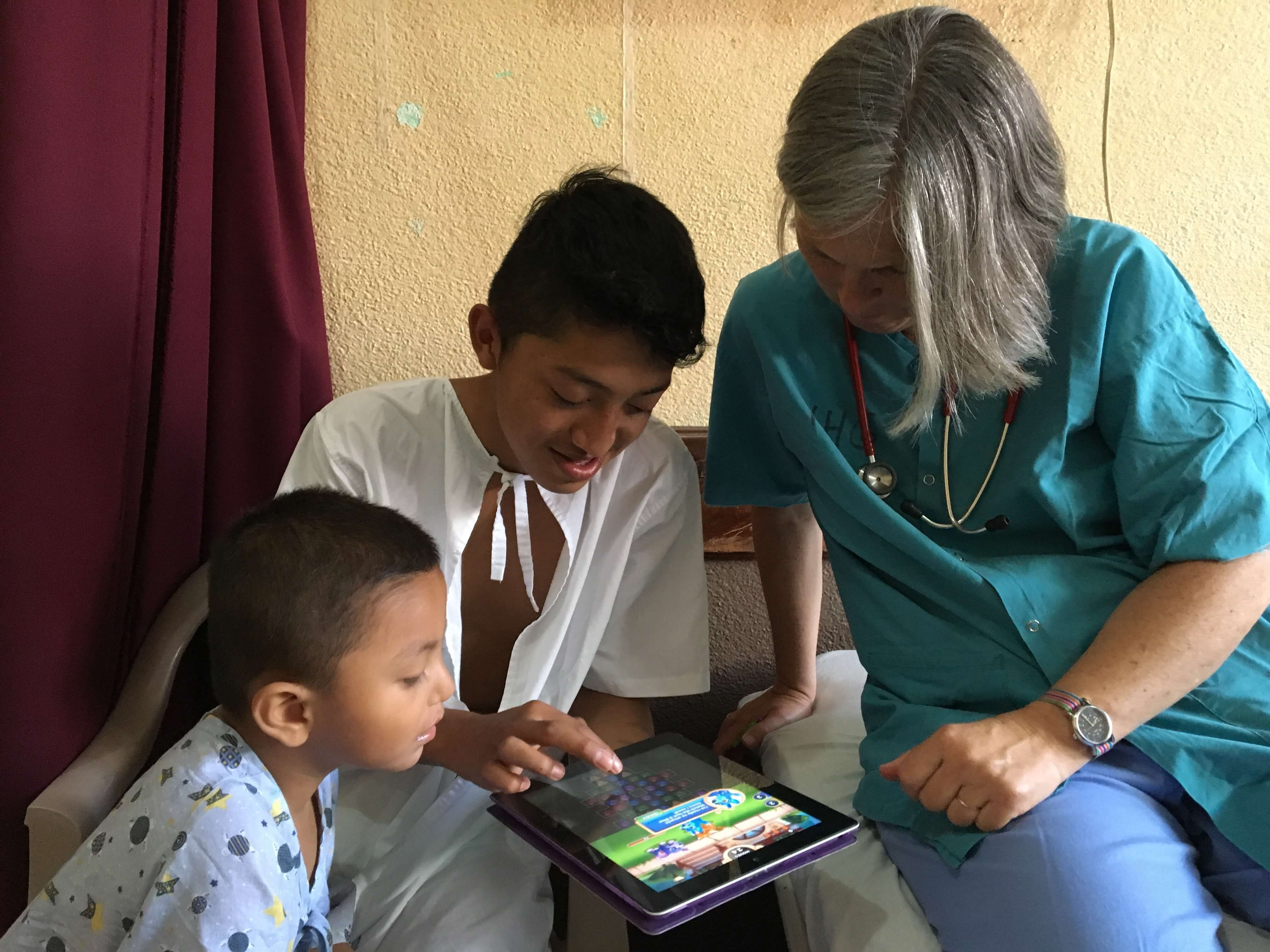 Robin and older patient Alex play a video game on Lead Pediatrician Paula Rand's iPad.