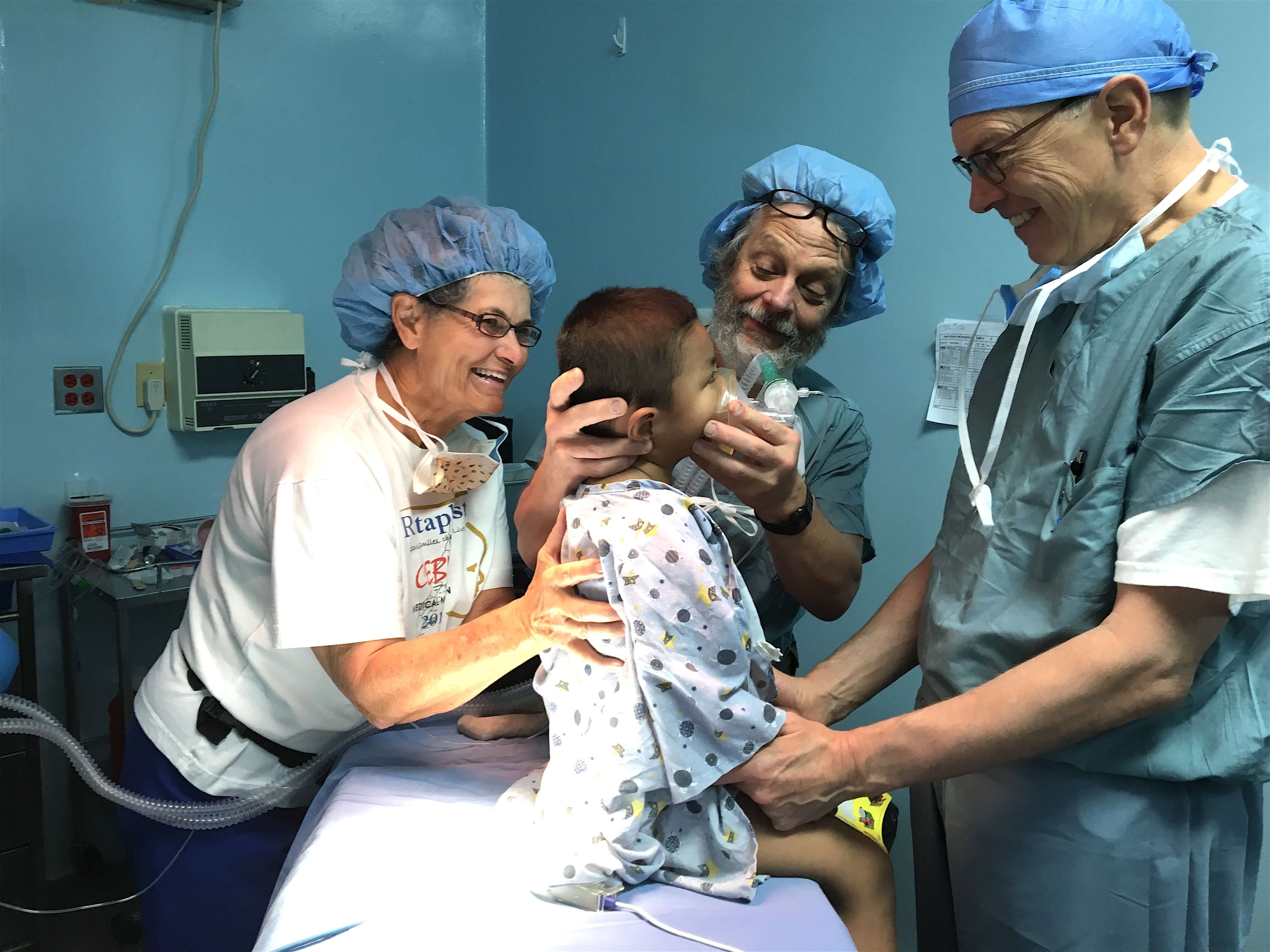 Lois, anesthesiologist Ken Kampman, and surgeon and Medical Director Rod Simonds prepare Robin for surgery.